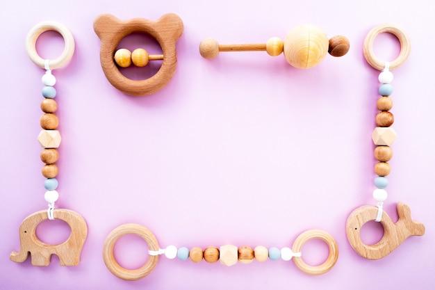 Eco-vriendelijk houten kinderspeelgoed op een roze achtergrond, bovenaanzicht, platte lay-out, kopie ruimte