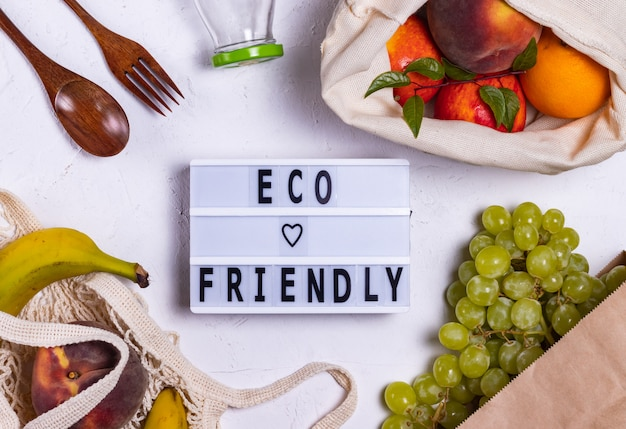 Eco-vriendelijk schreef op een bord in de buurt van fruit in eco-tassen
