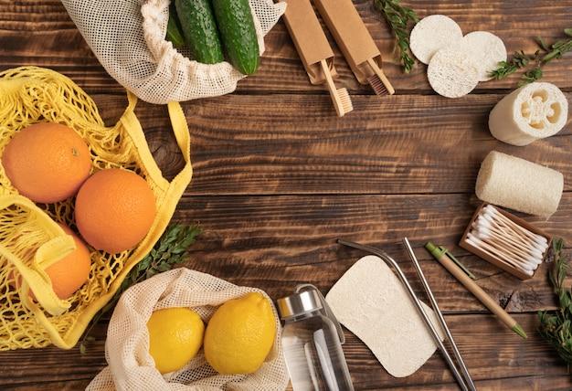 Eco-vriendelijke, afvalvrije platliggende, herbruikbare katoenen milieuvriendelijke tassen, bamboe tandenborstel, oorstokken, loofah-spons, biologisch afbreekbaar handvat op houten tafelmuur. maatschappelijke verantwoordelijkheid voor het milieu