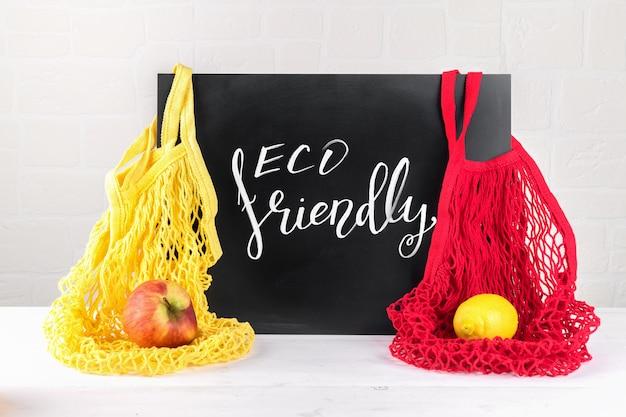 Eco-vriendelijke belettering, bericht op een zwart bord en katoenen tassen met twee koorden van gaas met appel en citroen, gebruik eco packeging in uw keuken, geen afval