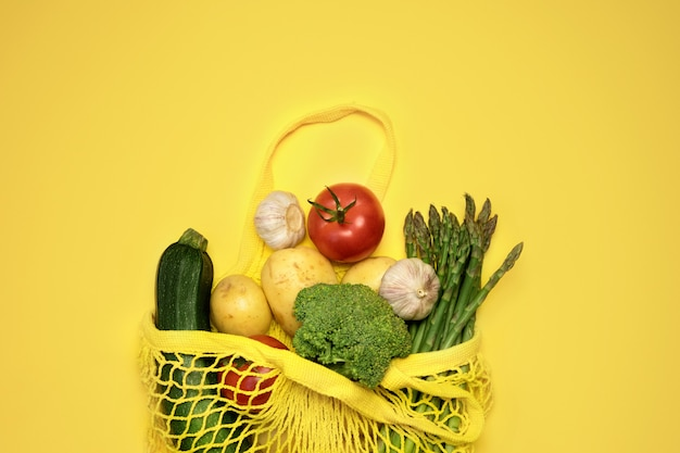 Eco-vriendelijke boodschappentas met groenten op geel