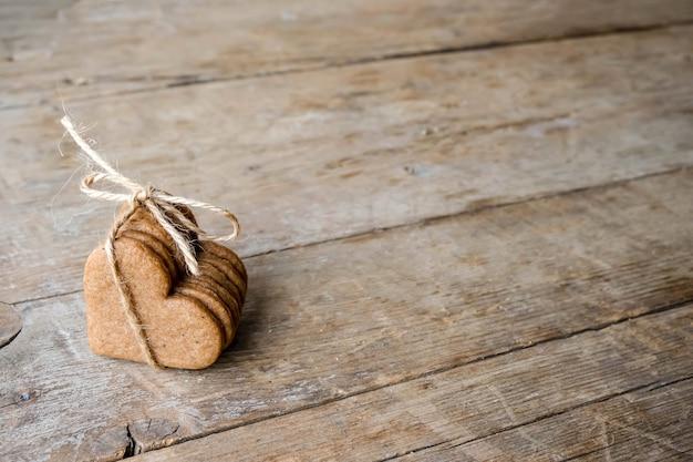 Eco-vriendelijke concept valentijnsdag plat leggen. koekjes vorm van heatrs gebonden jute touw op een houten achtergrond.