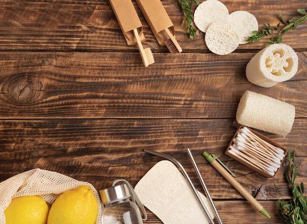 Eco-vriendelijke en afvalvrije platliggende, herbruikbare katoenen milieuvriendelijke tassen, bamboe tandenborstel, houten oorstokken, loofah-spons, biologisch afbreekbaar handvat op een houten tafelwand met kopie ruimte