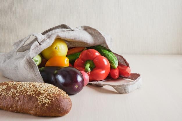 Eco-vriendelijke herbruikbare mesh string gebreide boodschappentas met fruit en groenten op tafel, zero waste concept