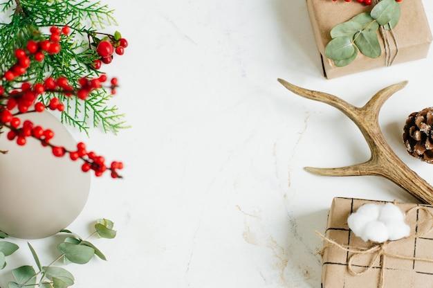 Eco-vriendelijke kerst versierd ambachtelijke papier geschenkdozen op witte marmeren achtergrond met lege ruimte voor tekst. bovenaanzicht, plat gelegd.
