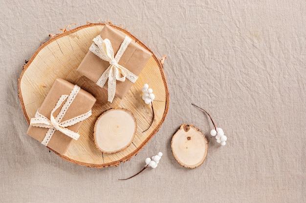 Eco-vriendelijke kerstcadeaus in scandinavische stijl verpakt in ambachtelijk papier met houten decoraties, plat gelegd, bovenaanzicht