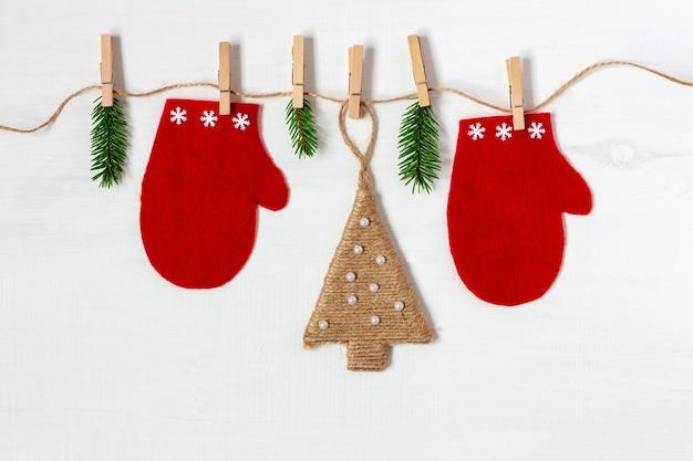 Eco-vriendelijke kerstmisslinger met rode wanten en handgemaakte boom op witte houten achtergrond