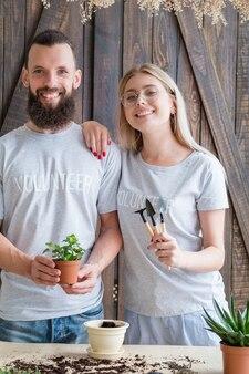 Eco-vriendelijke levensstijl. aanplant concept. glimlachend vrijwilligerspaar kamerplant en tuingereedschap te houden.