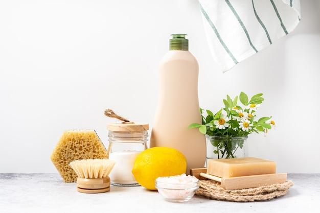 Eco vriendelijke natuurlijke reinigingsmiddelen pot met baking soda schotel borstel citroen bloemen zeep op witte achtergrond