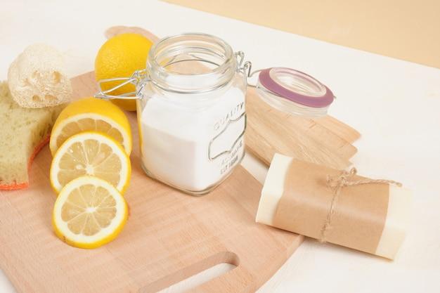 Eco-vriendelijke reinigingsset, frisdrank en citroen voor cleanong, zero waste lifestyle-concept. zuiveringszout in glazen pot, zeep, luffa en gesneden citroen op beige achtergrond