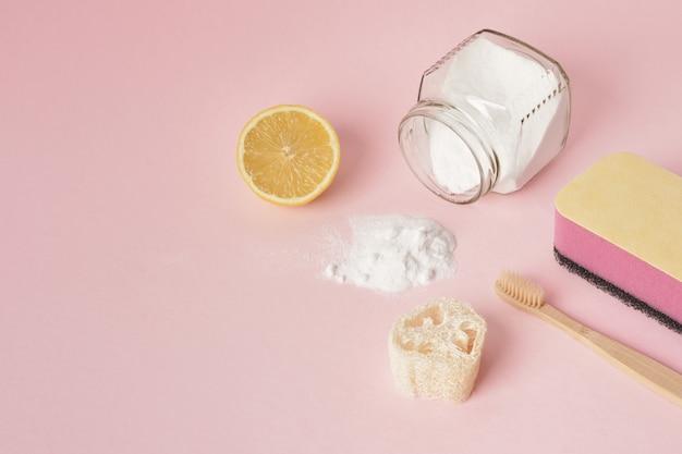Eco-vriendelijke schoonmaak concept handschoenen citroen en frisdrank op roze achtergrond