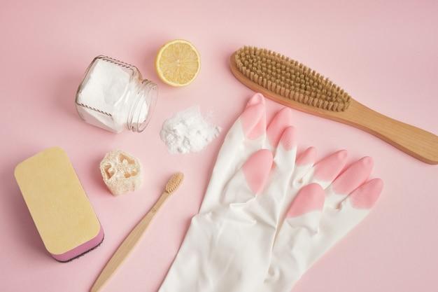 Eco-vriendelijke schoonmaak concept handschoenen houten borstel spons citroen en frisdrank op roze achtergrond