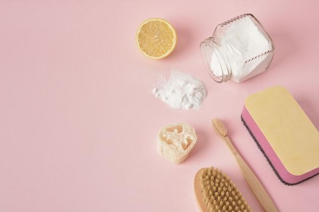 Eco-vriendelijke schoonmaak concept handschoenen houten spons citroen en frisdrank op roze achtergrond