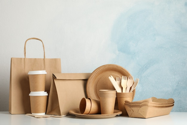 Eco-vriendelijke servies en papieren zak op witte tafel, ruimte voor tekst