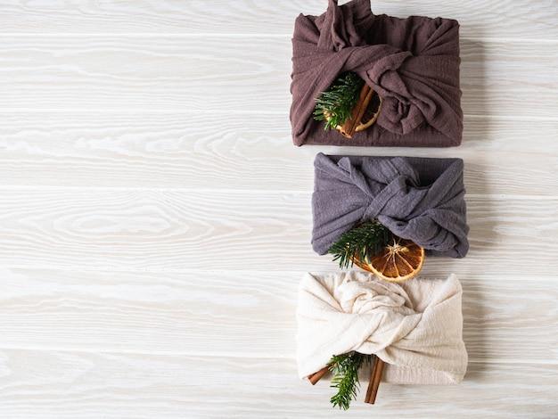 Eco-vriendelijke stoffen herbruikbare geschenkverpakkingen met fir brunch, kaneelstokje en droge sinaasappelschijf. alternatief herbruikbaar duurzaam cadeauverpakking voor kerstmis. geen afvalconcept. kopieer ruimte. bovenaanzicht