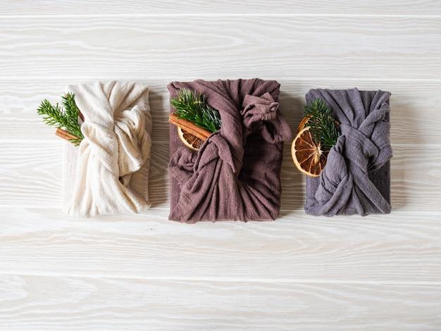 Eco-vriendelijke stoffen herbruikbare geschenkverpakkingen met fir brunch, kaneelstokje en droge sinaasappelschijf. alternatief herbruikbaar duurzaam cadeauverpakking voor kerstmis. geen afvalconcept. kopieer ruimte