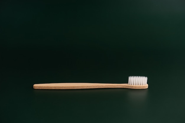 Eco-vriendelijke tandgezondheid antibacteriële bamboe houten tandenborstel op donkergroene achtergrond.