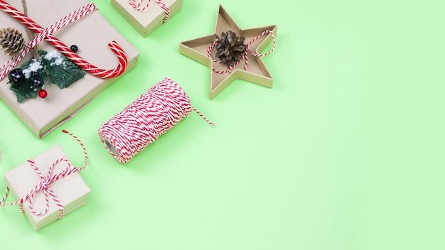 Eco-vriendelijke verpakkende kerstcadeaus op groen, eco kerstvakantie concept, eco decor met kopie ruimte. presenteer met snoep en dennenboom, papieren dozen en houten boomspeelgoed