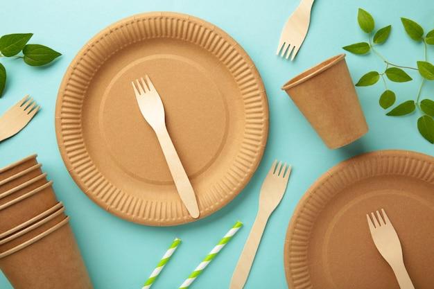 Eco vriendelijke wegwerp gerechten met groene bladeren op blauwe achtergrond. geen afval, milieuvriendelijke, plastic vrije achtergrond.