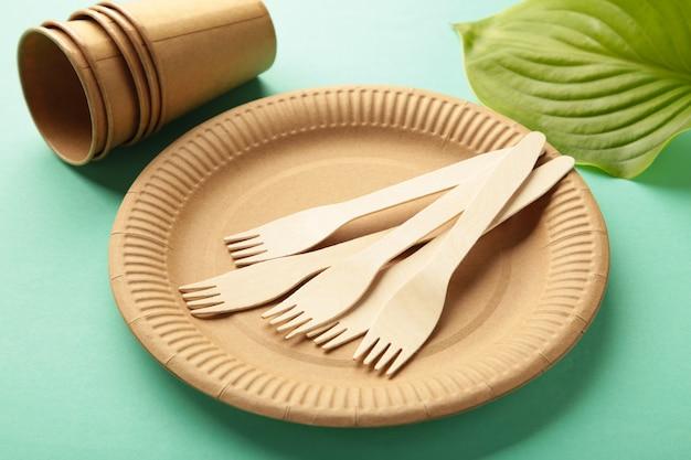 Eco vriendelijke wegwerp gerechten met groene bladeren op mint achtergrond. geen afval, milieuvriendelijke, plastic vrije achtergrond. bovenaanzicht