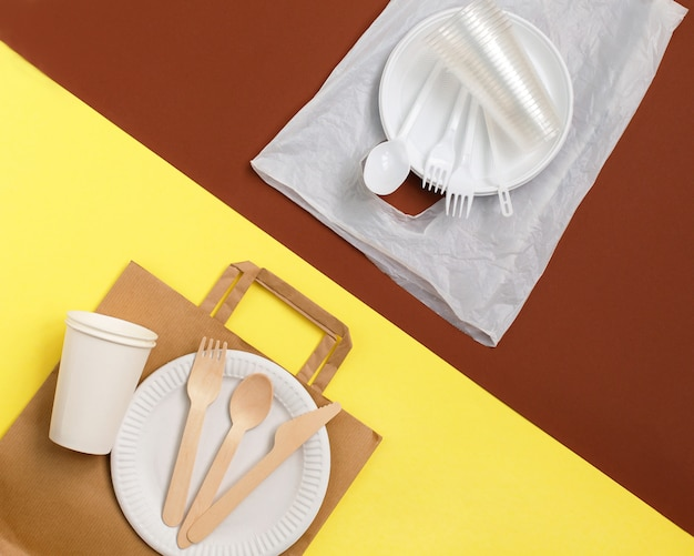 Eco-vriendelijke wegwerp servies gemaakt van bamboe hout en papier op een gele achtergrond
