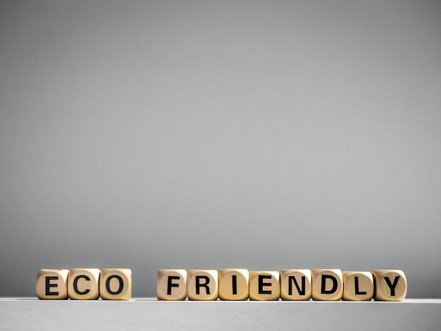 Eco-vriendelijke woorden op houten kubus op wit met kopie ruimte.