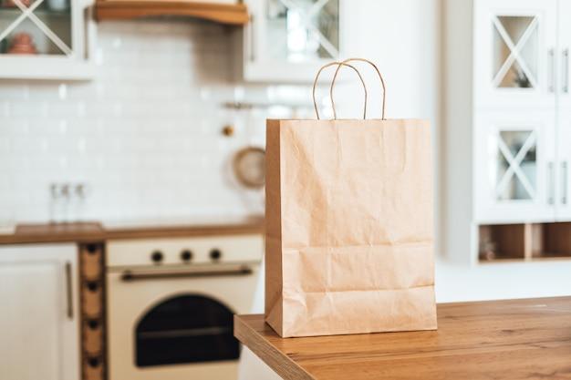 Eco winkelen papieren zak op tafel in de moderne keuken. levering van eten of winkelen op de markt.