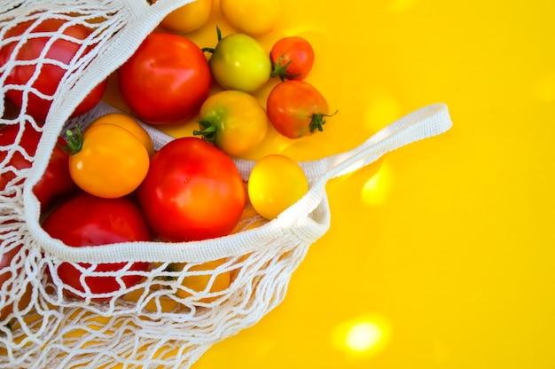 Eco winkelen veelkleurige tomaten in een katoenen milieuvriendelijke zak geïsoleerd op gele achtergrond