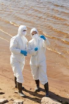 Ecologen in beschermende pakken die in team werken, staan naast de zee met een kolf en onderzoeken het water erin