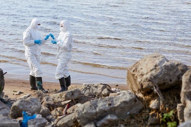 Ecologen in beschermende pakken staan bij de kust en nemen watermonsters voor analyse