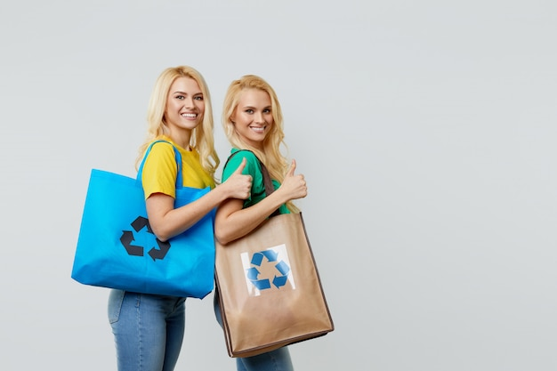 Ecologie concept. jonge vrouwen in vrijetijdskleding houden ecologische gerecyclede boodschappentassen op hun schouders.