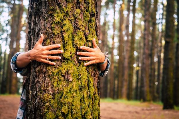 Ecologie en milieuconcept met blanke mensen die een groene boom knuffelen in het buitenbos