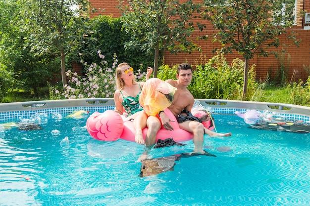Ecologieconcept - jonge man en vrouw die plezier hebben terwijl het milieu vervuild is, concept van een wereldwijd probleem met plastic afval dat in het water drijft.
