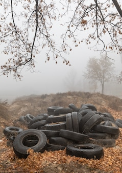 Ecologisch begrip. hoop oude banden. dump van oude gebruikte banden in de stad op een mistige herfstdag