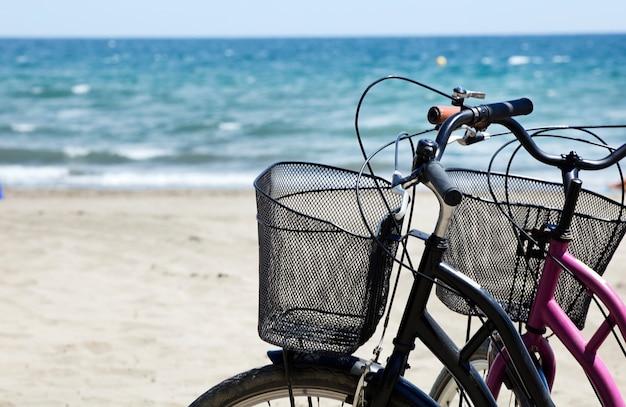 Ecologisch mobiliteitsconcept twee klassieke roze fietsen geparkeerd aan zee