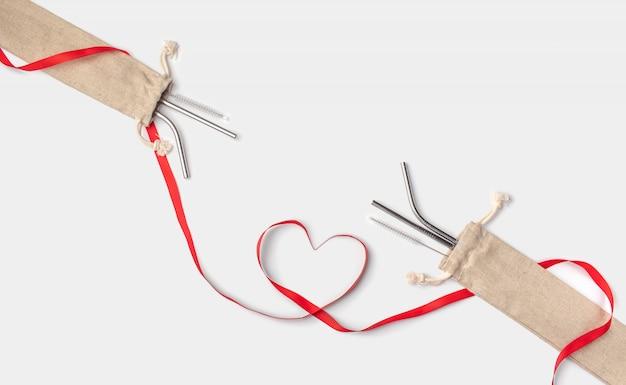 Ecologisch rvs rietjes in een linnen caseand rood hart lint op een witte achtergrond. geen afval, geen plastic, milieuvriendelijk. red de planeet