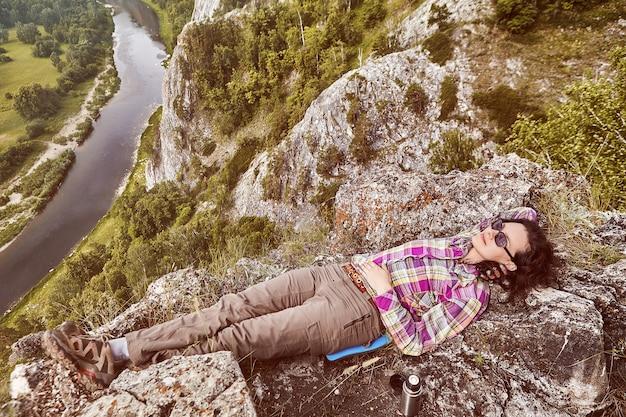 Ecologisch toerisme in bergen, mooie blanke vrouw berust bovenop berg boven rustige rivier.