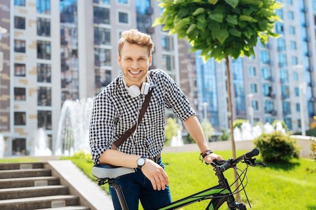 Ecologisch voertuig. opgetogen, aangename man die op zijn fiets leunt terwijl hij naar je kijkt