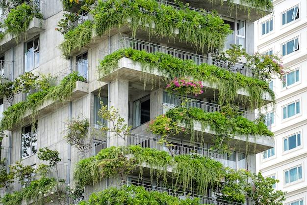 Ecologische gebouwen gevel met groene planten en bloemen op stenen muur van de gevel van het huis op de straat van danang, vietnam