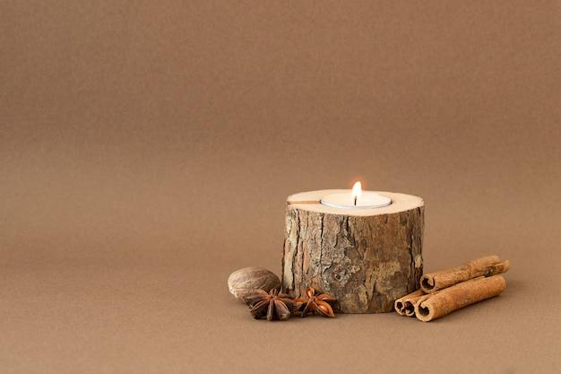 Ecologische kaars met licht, kaneelstokjes, anijssterren en nootmuskaat Premium Foto