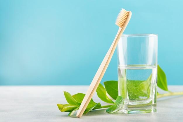 Ecologische tandenborstel gemaakt van natuurlijk bamboe, een glas water en een tak met boombladeren op een blauwe achtergrond