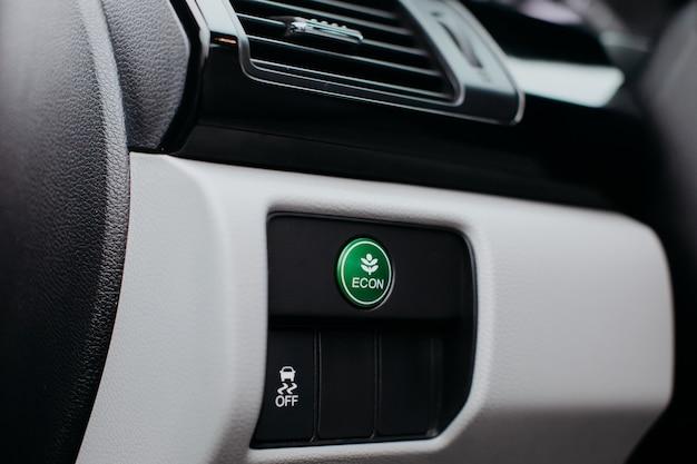 Econ-modusknop op dashboard in moderne auto. eco-modus, groene knop.