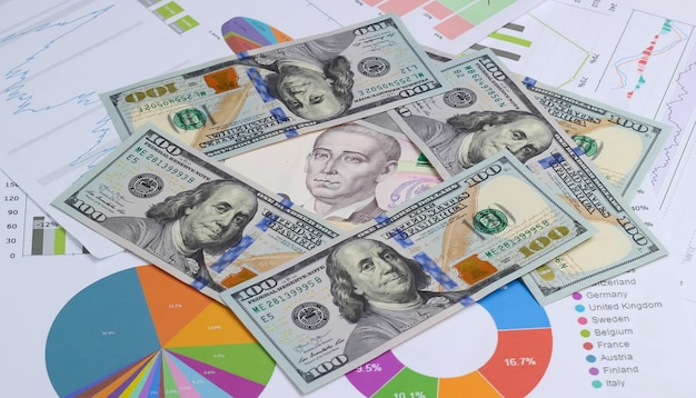 Economische voorspelling van groei en val van de munt. dollarbiljetten en oekraïense hryvnia tussen grafieken en diagrammen