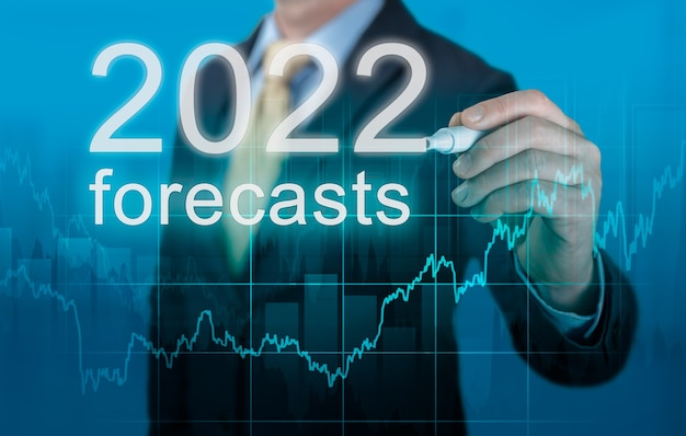 Economische voorspellingen voor 2022. zakenman schrijft voorspellingen voor 2022 op virtueel scherm. nieuwjaarsvoorspellingen voor 2022. zakenman in pak prognose analyse plan winstgrafiek met pen