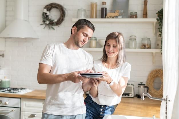 Economische vrouw afwas en het overhandigen aan de ijverige man om thuis in de keuken af te vegen