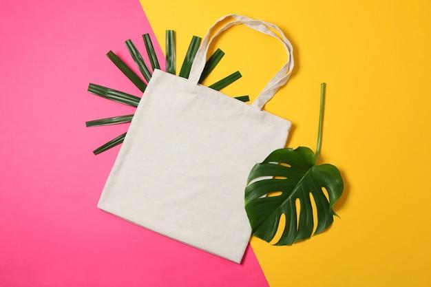 Ecotas en palmbladen op kleurenachtergrond