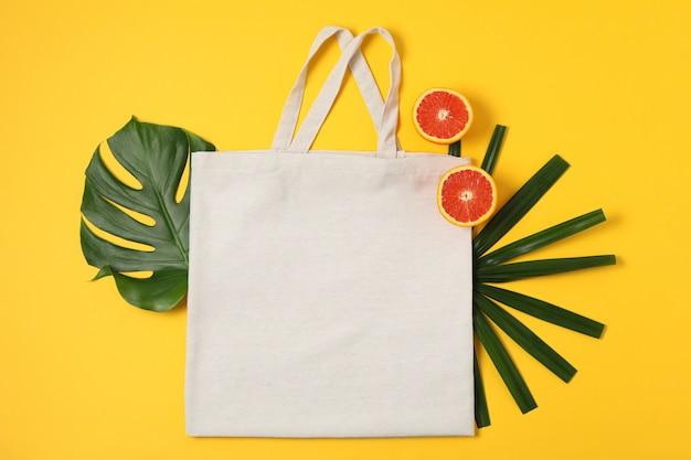 Ecotas, palmbladen en sinaasappel op kleurenachtergrond