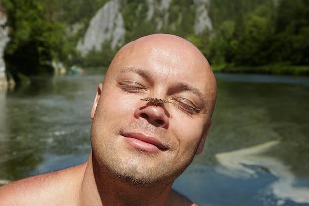 Ecotoerisme in ecosysteem van bosrivier, kale man sloot zijn ogen en zette zijn gezicht op de zon, kleine bruine vlinder zit op zijn neus. Premium Foto
