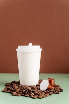Ecovriendelijke wegwerp witte papieren beker met koffiebonen en capsules, mock-up ontwerp