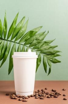 Ecovriendelijke wegwerp witte papieren beker met tropisch blad en koffiebonen, mock-up ontwerp